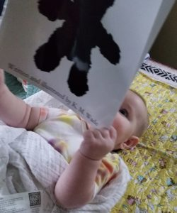 Black and white baby book for newborns: This 3-month-old loves the personalised black and white picture book for newborns 'Where's My Teddy?'. He's holding it and gazing at it intently.